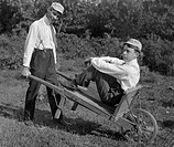 Two men with an old wheelbarrow, historical image, ca. 1927