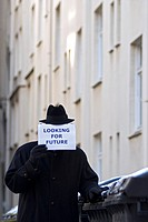 Man holding a sign with the message, Looking for future, symbolic image for the economic crisis
