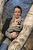 French Bulldog Canis lupus f. familiaris, woman leaning at a tree with welp on her arms