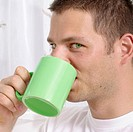 young man drinking out of a coffee cup