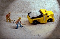 Two construction figures shovel sand into the back of a yellow pick up truck