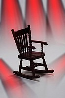 A rocking chair against a white background with red spotlights streaming down