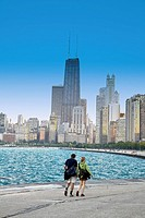 A young couple walk hand in hand along the lakefront  The Chicago skyline is in front of them  Watercolor sketch effect applied