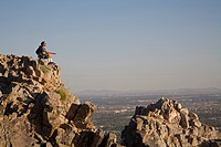 A hiker meditates in the late afternoon sun at the top of Piestewa Peak, Phoenix, Arizona, USA