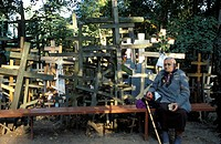 Senior woman sitting by large group of crosses at Festival of Crosses