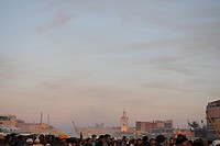 Crowd, skyline of city in background, sunset
