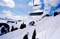 Chairlift over snow covered mountain with pine trees