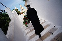 Orthodox priest walking up stairs, Corfu