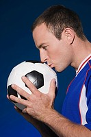 Footballer kissing a football