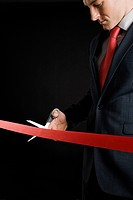Businessman cutting a red ribbon