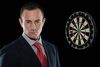 Businessman standing next to a dartboard
