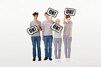 People holding signs that say ok