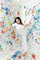 Woman with leg raised and walls covered in paint