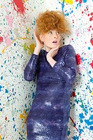 Young woman in sequin dress and paint covered walls