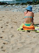 Young woman in bikini sitting on towel at the beach