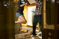 Young couple jumping on bed