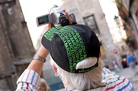 Elderly male tourist in souvenir hat videoing cathedral