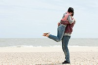 Man by the sea lifting up girlfriend