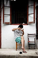 a kid eats rice at the door of his house. Shanghai, China