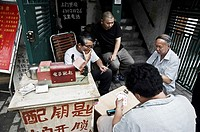 a group of men playing cards in the street. Shanghai, China
