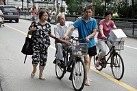 an elder is transported by bicycle. Shanghai, China