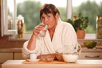 Woman having breakfast drinking glass of water / bowl, cup of coffee, pot of milk, muesli