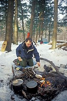 Porcupine Mountains State Park, Michigan - Alan Jacobson cooks over an open fire during a winter camping trip in the Porcupine Mountains