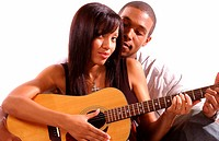 young man teaching his girlfriend how to play guitar