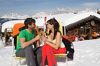 couple in love drinking champagne near alpine hut