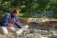Quetico Provincial Park, Ontario - Sue Welch, 70, cuts wood for a campfire while on a canoe camping trip