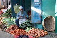 Mysore, Karnataka, India. Muslim man reading a newspaper at his vegetable stall at the Devaraja Market. The Devaraja Fruit &amp; Vegetable Market on Sayya...