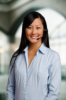 A corporate receptionist greets a customer