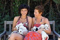 two young girls with a dog puppies of the English Setter breed