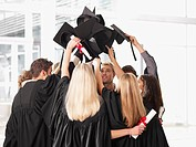Graduates in huddle holding mortarboards overhead