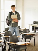 Confident college student standing in classroom