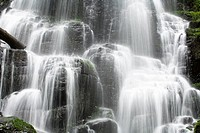 Blurred motion shot of remote waterfall splashing in forest