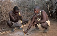 Hadzabe man making a fire with a stick and stone, Tanzania, Lake Eyasi
