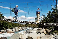 Hikers crossing a suspension bridge in the Valle del Frances, Torres del Paine National Park, Patagonia, Chile, South America