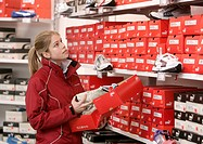 Customer looking at sport shoes, trainers, in the Puma outlet store in Herzogenaurach, Bavaria, Germany, Europe