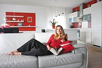 young beautiful woman sitting on soffa in modern kitchen interior