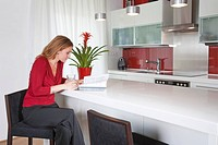 young beautiful woman sitting in modern kitchen interior