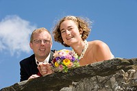 Bride and groom leaning on an old castle wall, holding a bouquet of flowers