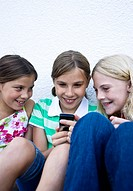 Three girls looking at a mobile phone