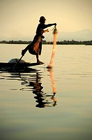 Fisherman, rowing his boat with one leg, at dusk, near Nyaung Shwe, Inle Lake, Shan State, Burma, Myanmar, Southeast Asia
