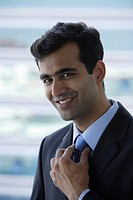 Head shot of Indian businessman smiling.