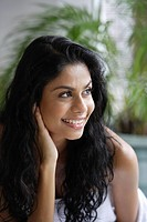 Profile of Indian woman smiling and touching her hair/