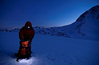 Aided by a headlamp, a mountaineer looking for something in your bagpack. Pe&#241;a Ubi&#241;a, Castilla-Le&#243;n, Spain