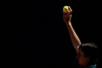 Ball boy holding up a tennis ball