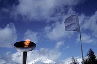 Olympic torch with snow topped mountain in background