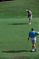 Golfer watches as player putts his shot